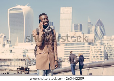 Young black man talking on mobile phone in London with city skyscrapers on background in a sunny day. He is wearing a coat and has a vintage backpack. Vintage filter applied. - stock photo