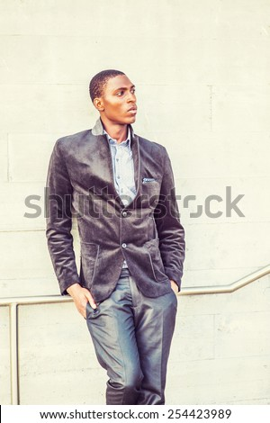 Young black man thinking outside. Wearing a fashionable jacket, a young black college student standing against the wall, looking away, thinking. Concept of teenager self esteem. Retro filtered look. - stock photo