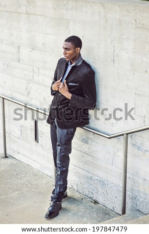 Young black man thinking outside. Wearing a white under wear, fashionable jacket, a young black college student is standing against the wall, seriously thinking. Street Fashion. - stock photo