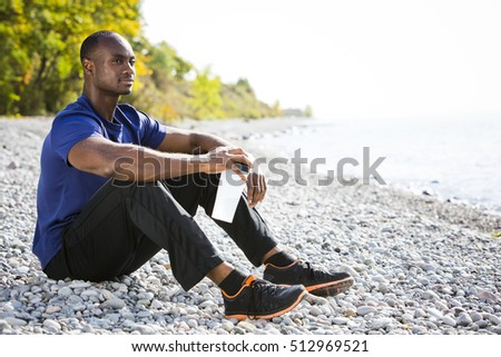 young black man wearing athletic wear sitting on the beach