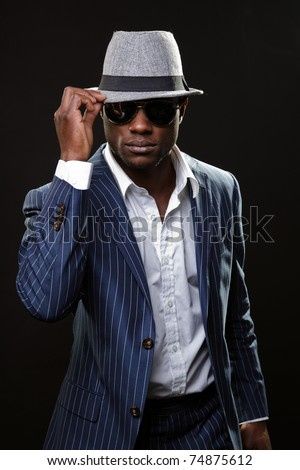 Young black man wearing suit and hat and sunglasses. - stock photo