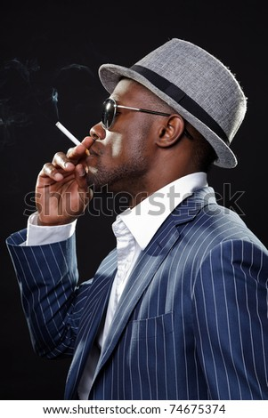 Young black man wearing suit and hat and sunglasses. Smoking a cigarette. - stock photo