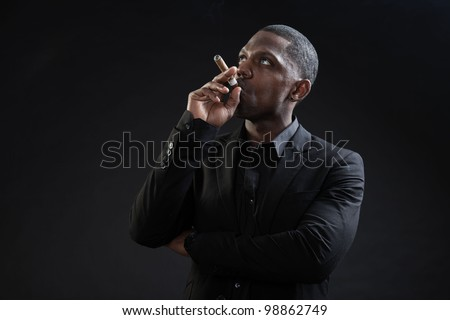 Young black man wearing suit gangster style smoking cigar isolated on dark background. Studio portrait. - stock photo