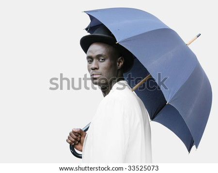 Young black man with a blue umbrella wearing a bowler hat. - stock photo