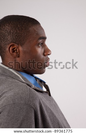 Young black man with a gray sweater, smiling at the camera with pleasure and joy - stock photo