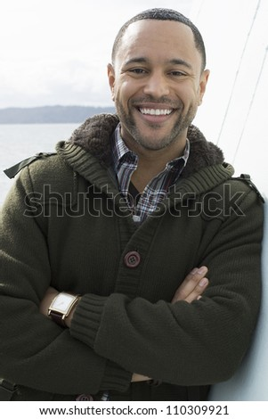 Young black man with smile on boat deck, leaning against wall with water in the background. - stock photo