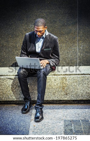 Young black man working outside. Dressing in a blazer, pants, leather shoes, a young black guy is sitting on a marble stone bench, looking down, working on a laptop computer.  - stock photo