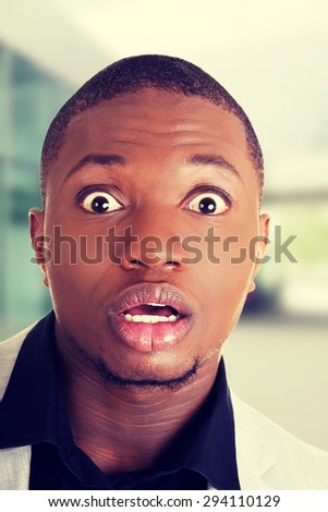 Young black shocked businessman wearing suit