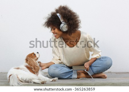 young black student using electronics in garden with her dog - stock photo