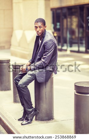 Young black teenage boy is sitting on street, hunchbacked, sad, tired, looking at you. Man relaxing outside. Retro filtered look.   - stock photo