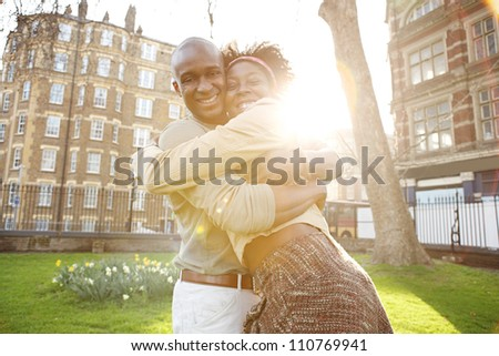 Young black tourist couple passionately hugging in a park, laughing and having fun.