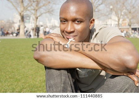Young black tourist man sitting down on green grass in the city of London while on vacation, smiling and resting his head on his arms.