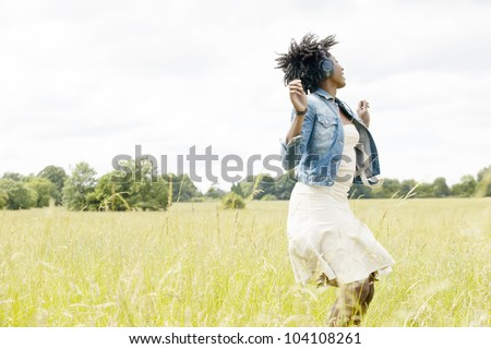 Young black woman dancing in a long grass field while listening to music with her headphones. - stock photo