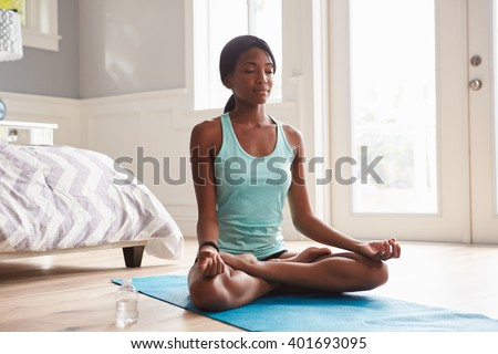 Young black woman doing yoga at home in the lotus position - stock photo