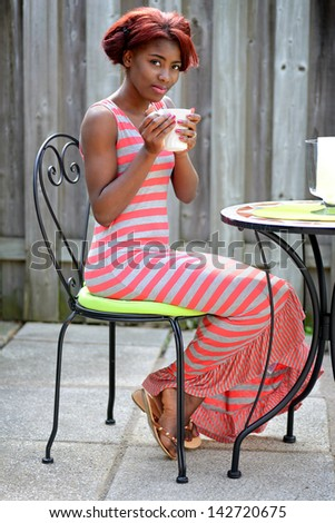 young black woman enjoying coffee on the patio - stock photo