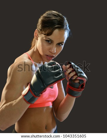 Young black woman fighter wearing gloves isolated on a dark background