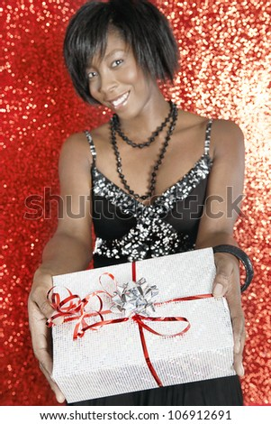 Young black woman holding a silver gift towards the camera, smiling on a red glitter background.