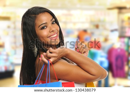Young Black Woman Holding shopping bags and smiling isolated on a white background