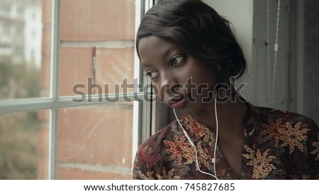 Young black woman listening music travelling looking outdoor the window, pensive - thoughtful, thinking future, music concept, african american student think about home