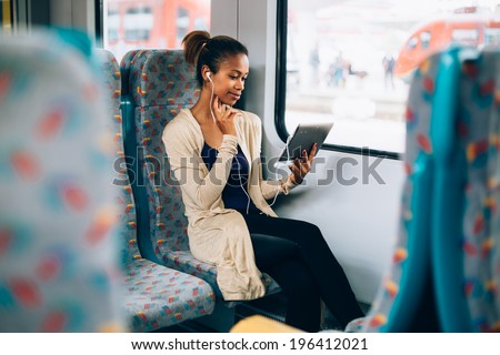 Young black woman listening to music on train using tablet computer - stock photo