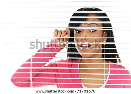 Young black woman looking through horizontal venetian blinds - stock photo