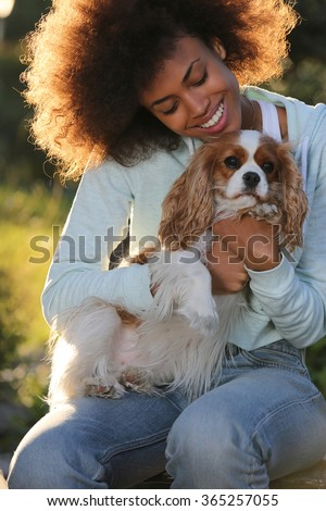 young black woman playing with her dog in park sunset.