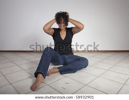 Young black woman pulling her hair out. - stock photo