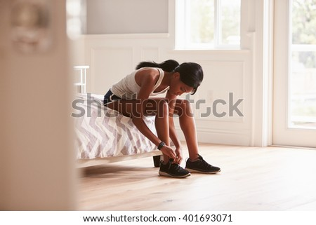Young black woman ready for exercising tying her sports shoe - stock photo