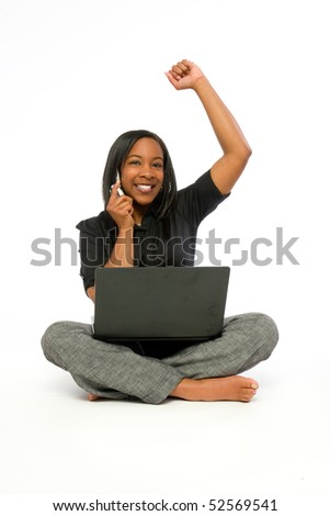 Young black woman seated with computer on lap talking on cell phone. - stock photo
