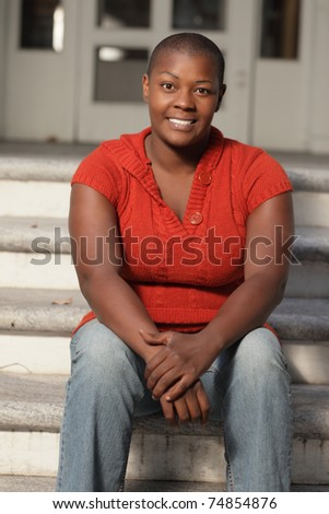 Young black woman sitting on a staircase - stock photo