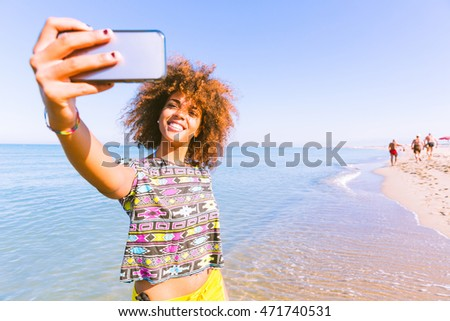 Young black woman taking a selfie at beach.  Twenty years old girl, mixed race caucasian and african black with curly hair. Travel and vacations concepts. Color filter added.