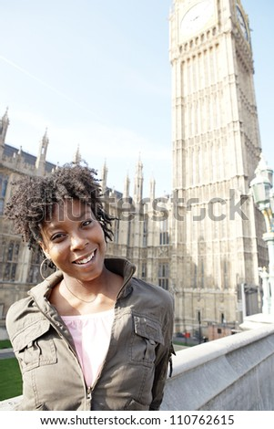 Young black woman tourist visiting Big Ben in London with a blue sky. - stock photo