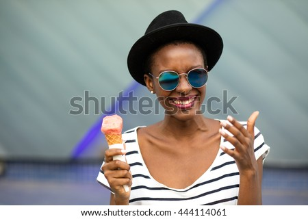 young black woman with hat, sunglasses and striped shirt eating ice-cream, very happy somewhere in the city - stock photo