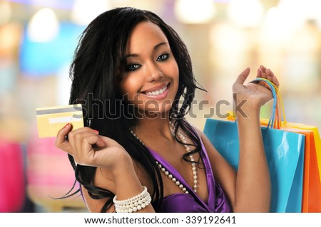 Young Black woman with shopping bags and credit card inside a mall - stock photo