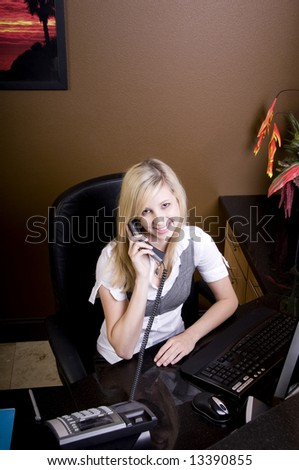 Young blond adult on phone sitting behind desk in white T-shirt and petite vest.