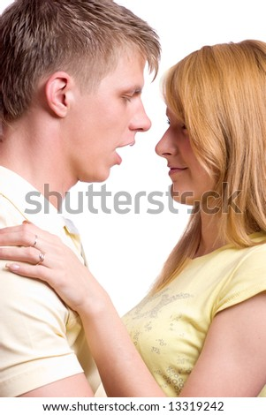Young blond beautiful couple going to kiss isolated on white