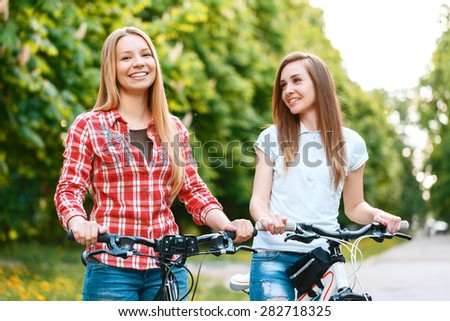Young blond beautiful girl and her charming friend standing smiling near their bikes holding the handlebars wearing jeans green park on the background - stock photo