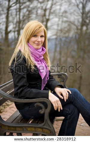 Young blond beautiful girl sitting on the bench
