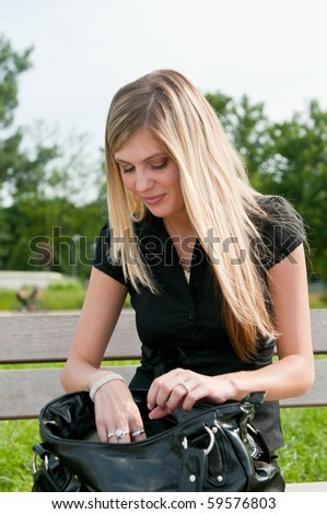 Young blond beautiful woman looking for something in her big hand bag