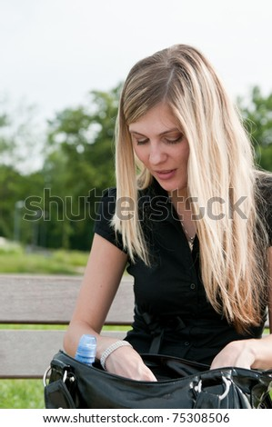 Young blond beautiful woman looking for something in her big hand bag - stock photo
