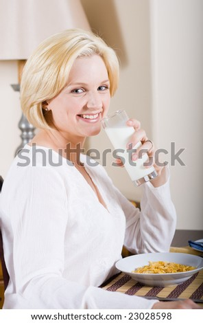 young blond beautiful woman sitting by breakfast table and drinking glasses of milk - stock photo