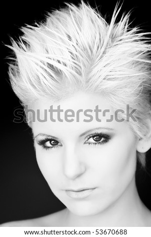 Young blond beauty portrait over black background.