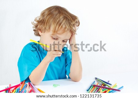 Young blond boy draws with color pencils on a white background