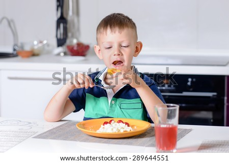 Young Blond Boy Eating Plate of Cheese and Fruit with Spoon While Sitting at Kitchen Table