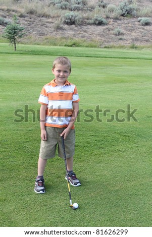 Young blond boy standing in the fairway before his shot - stock photo