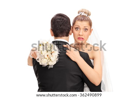 Young blond bride hugging her husband with her fingers crossed isolated on white background - stock photo