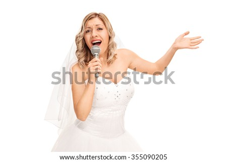 Young blond bride in a beautiful white wedding dress singing on a microphone isolated on white background - stock photo