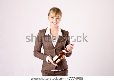 young blond business woman with a bottle champagne - stock photo