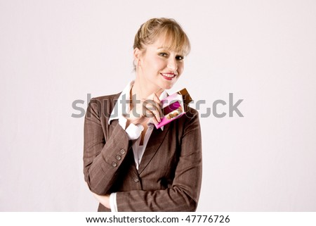young blond business woman with a chocolate bar - stock photo
