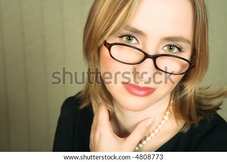 Young blond business woman with pearl necklace and green eyes looking with tired green eyes over her glasses - stock photo